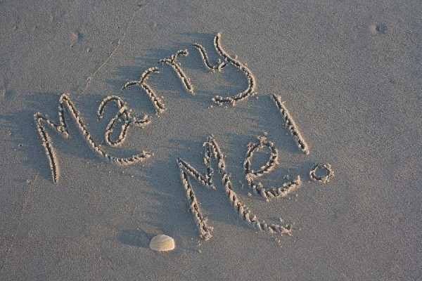 Marry me text on sand beautiful art