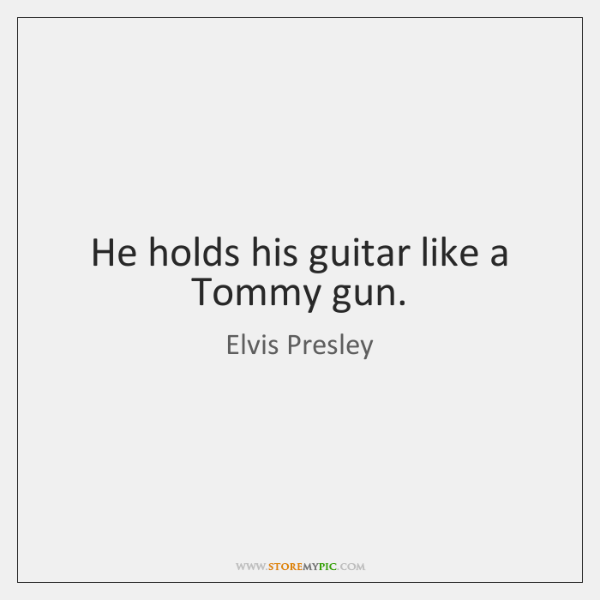 He holds his guitar like a Tommy gun.