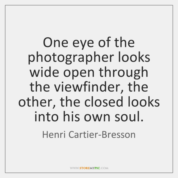 One eye of the photographer looks wide open through the viewfinder, the ...